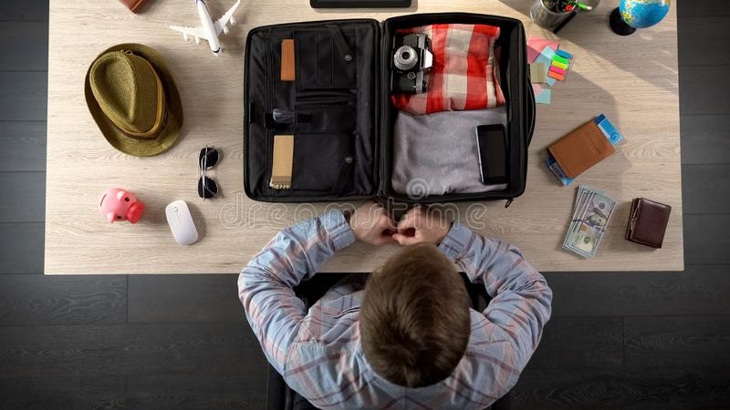 Man carefully packing suitcase, preparing for business travel, official journey stock photo