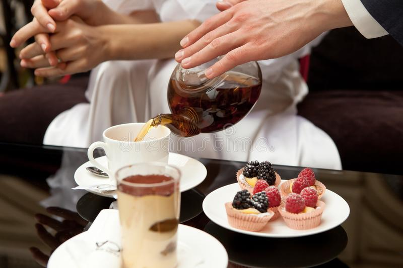 A man cares for a woman: pours her green tea. On the table are desserts: tiramisu and pastries with fresh berries. Without faces. In the frame of the hand stock photo