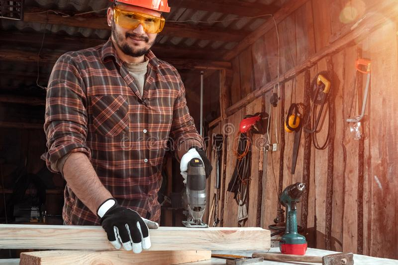A man carpenter cuts a wooden beam using an electric jigsaw, male hands with an electric jigsaw closeup. Work with wood royalty free stock photo