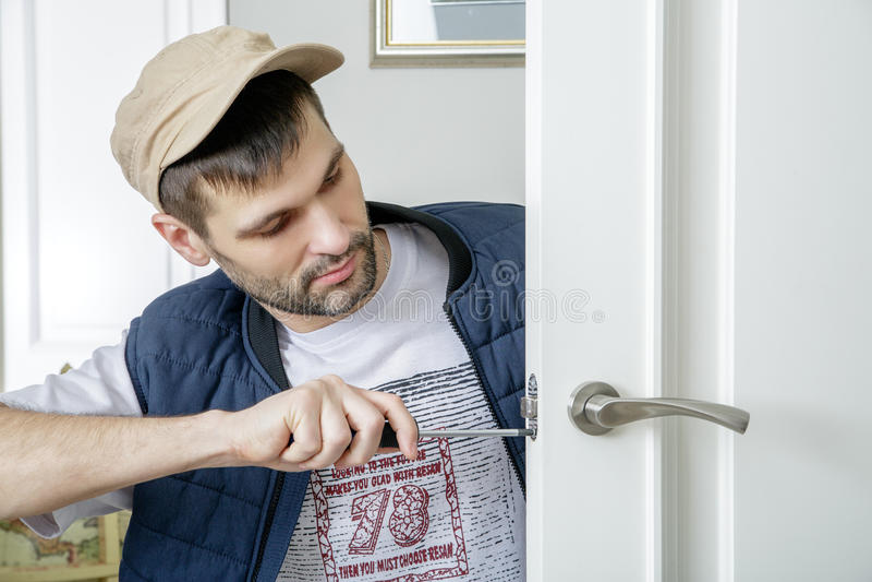 Man carpenter fixing lock in door with screwdriver at home. stock photo