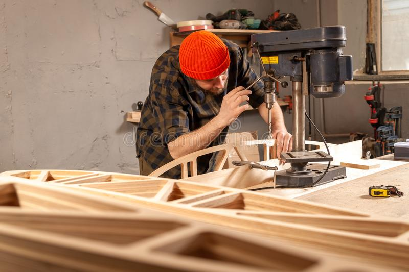 Construction Worker. A man carpenter in a hat and a shirt  is carving a wooden board on a large drilling machine in a workshop side view, in the background a lot royalty free stock images