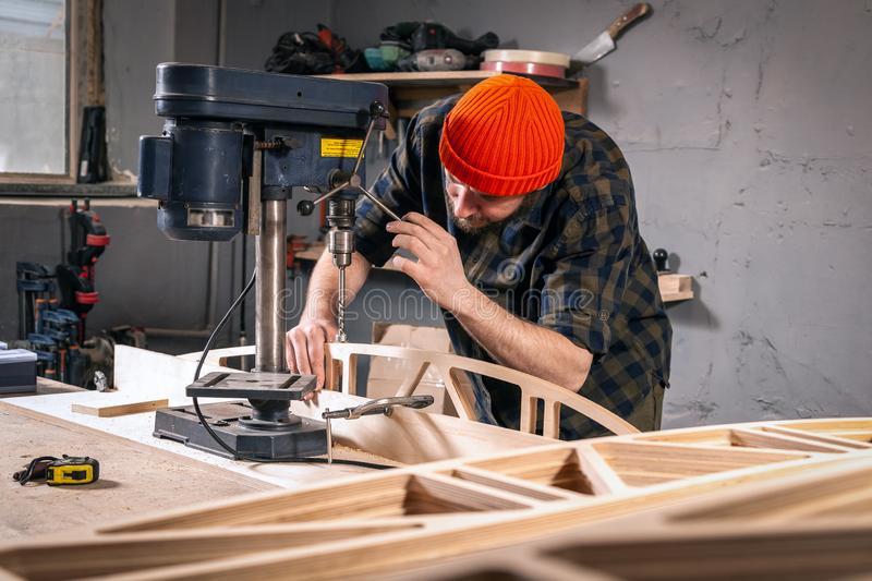 Construction Worker. A man carpenter in a hat and a shirt  is carving a wooden board on a large drilling machine in a workshop side view, in the background a lot stock photo