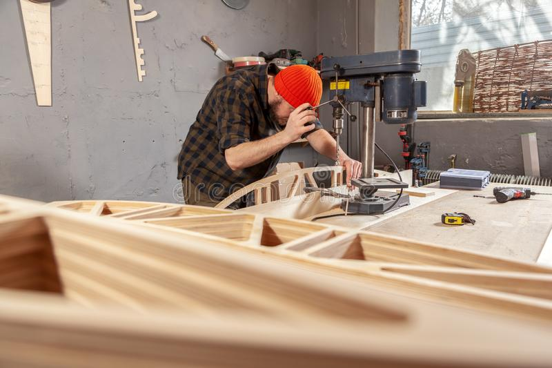 Construction Worker. A man carpenter in a hat and a shirt  is carving a wooden board on a large drilling machine in a workshop side view, in the background a lot stock photos