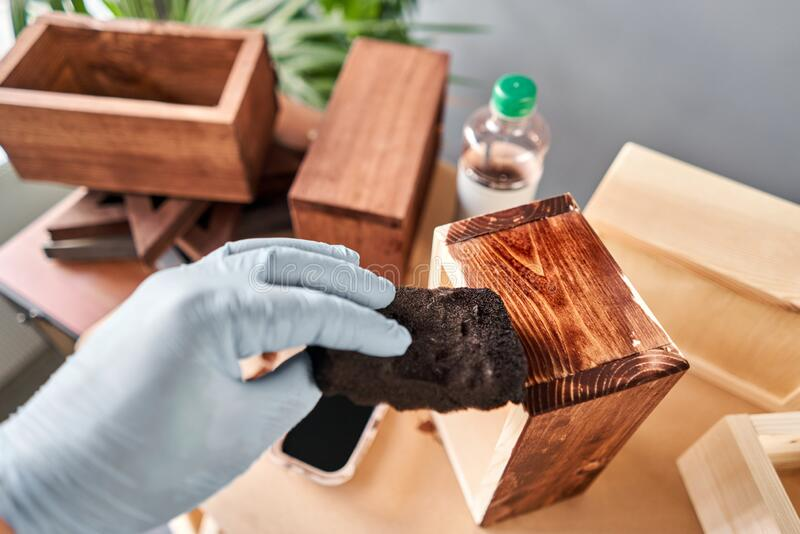 Man carpenter varnishing wooden crate for flowers with brush in her small business woodwork workshop. In your work, do royalty free stock photography