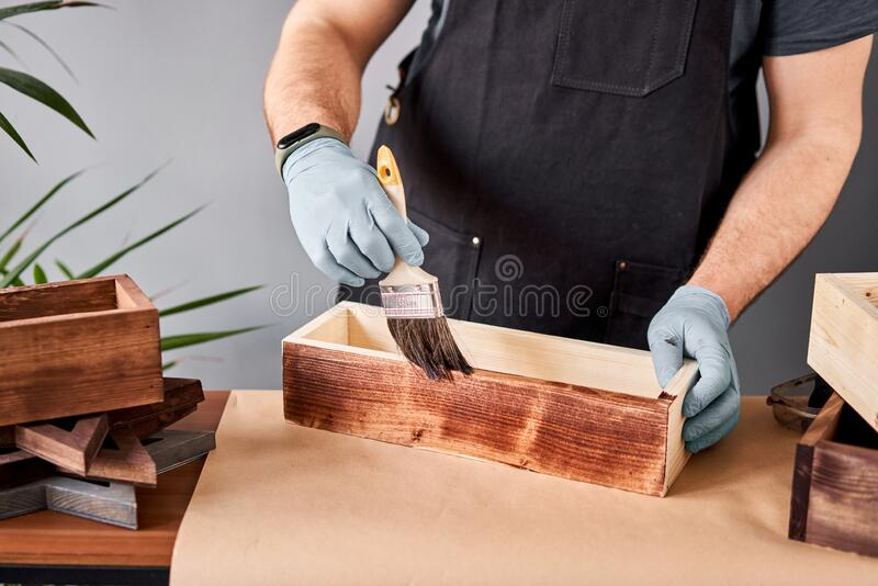 Man carpenter varnishing wooden crate for flowers with brush in her small business woodwork workshop. In your work, do stock image