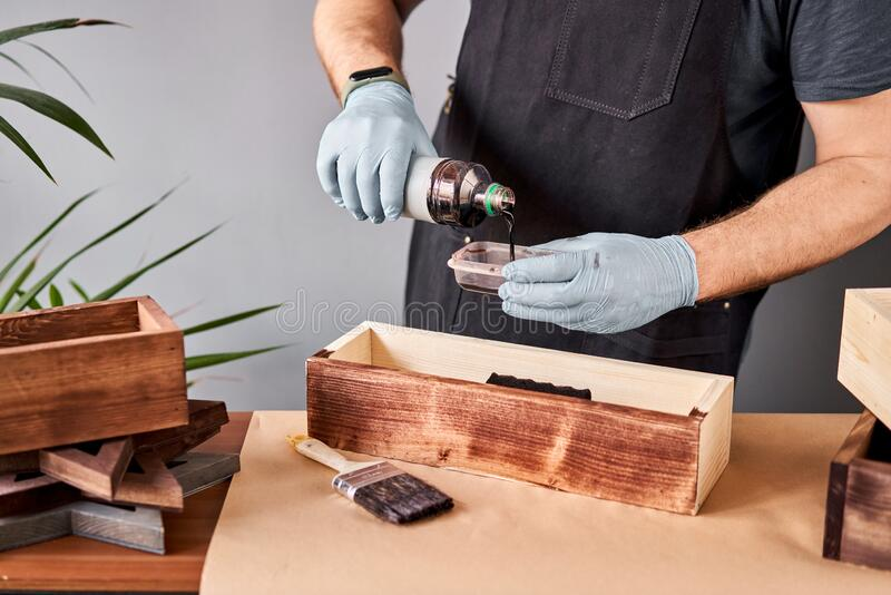 Man carpenter varnishing wooden crate for flowers with brush in her small business woodwork workshop. In your work, do stock images