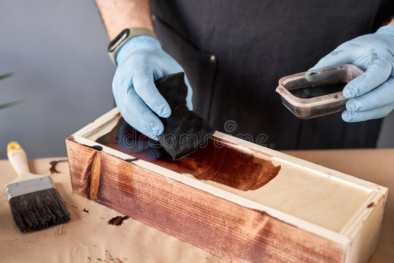 Man carpenter varnishing wooden crate for flowers with brush in her small business woodwork workshop. In your work, do stock photos