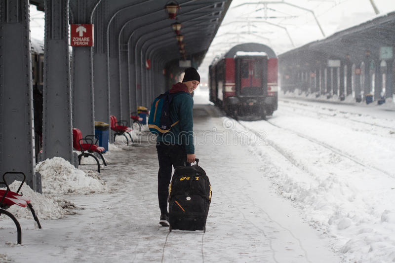 Man carries his baggage on heavy snow storm. Bucharest, Romania - January 7, 2017: Rear view of young Caucasian man carrying his trolley towards his train during royalty free stock image