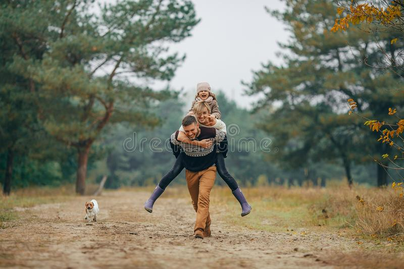 Man carries his wife and daughter on his back at forest path next to dog during walk. Happy family has fun and men carries his wife and daughter on his back at stock photos