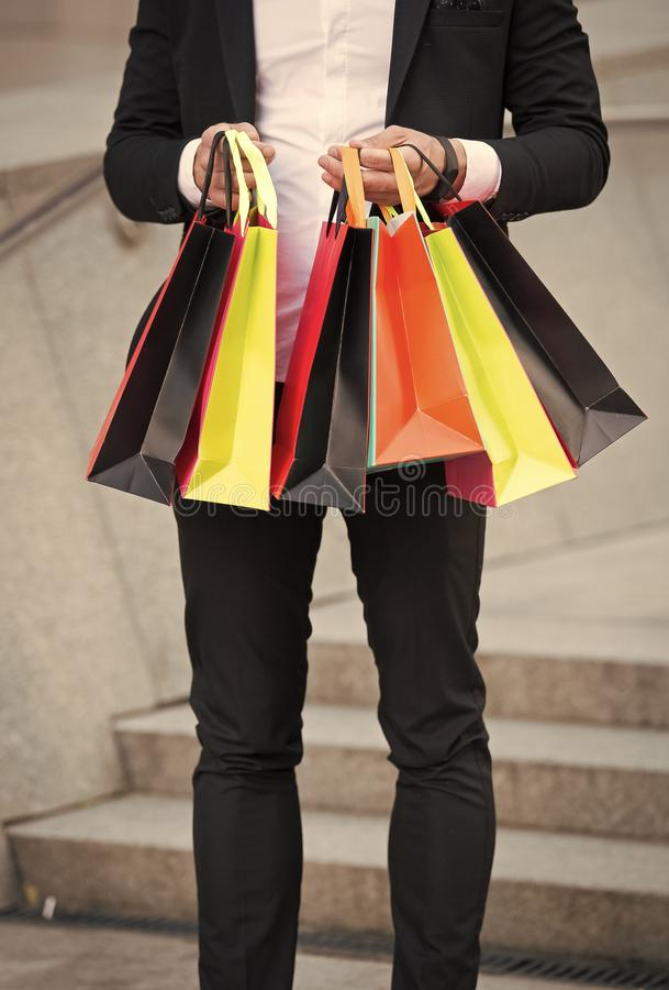 Man carries shopping bags urban background. Successful businessman shopping online. Busy people appreciate online stock photography