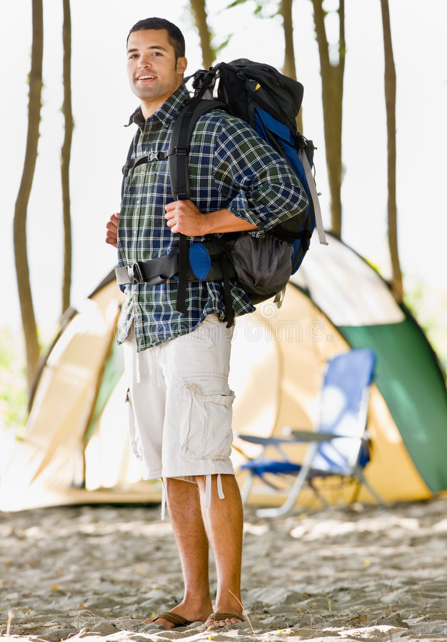 Man carrying backpack at campsite. Man carrying backpack at a campsite royalty free stock photography