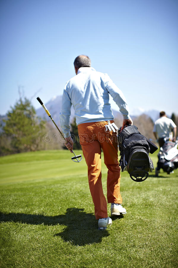 Man carrying a bag with golf clubs. On a golf course royalty free stock photo
