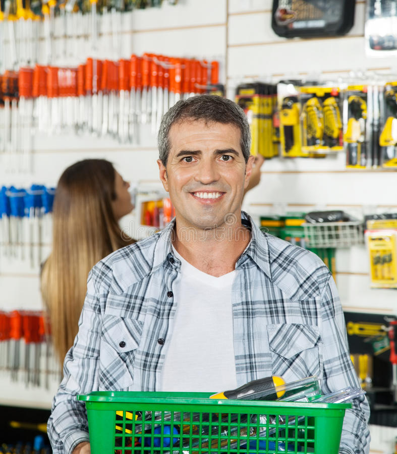 Man Carrying Basket Full Of Tools In Store stock image