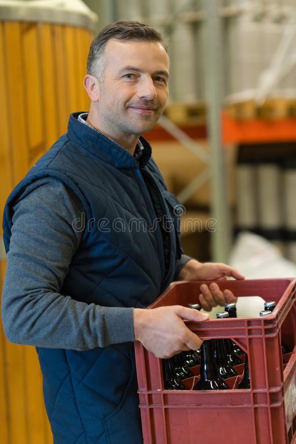 Man carrying beer boxes in brewery. Man carrying beer boxes in a brewery royalty free stock photos