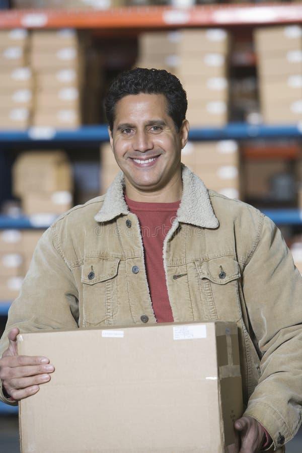 Man Carrying Cardboard Box In Warehouse stock photo