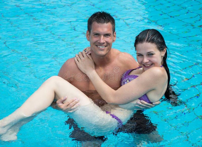 Man carrying girl at swimming pool. stock image