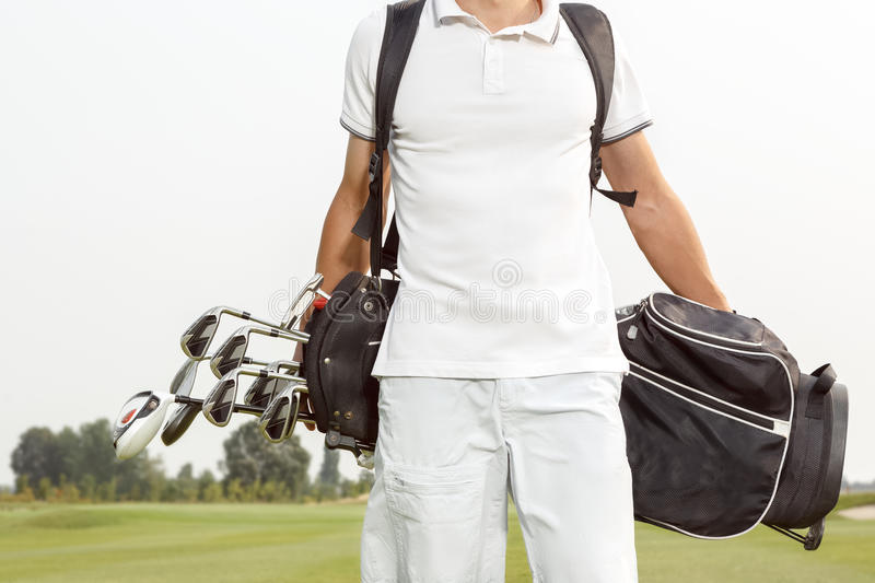 Man carrying his golf bag across course royalty free stock image