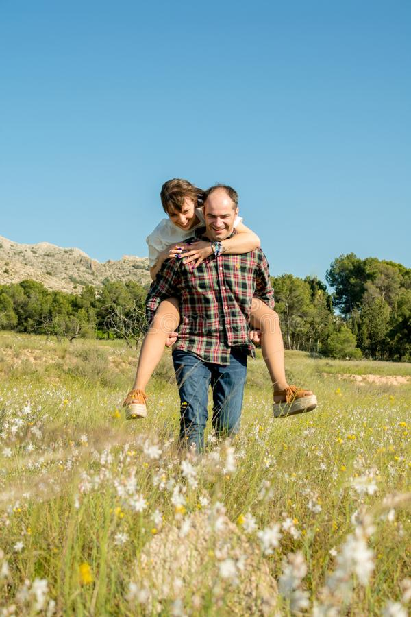 Man carrying his wife piggyback on his back royalty free stock photography