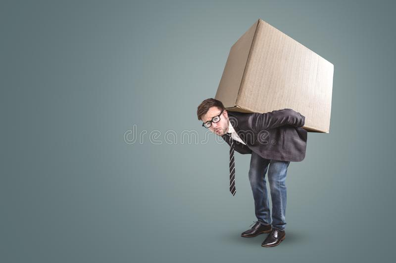 A man is carrying a large cardboard box - isolated on a neutral background with copy space. A man in a jacket and tie is standing bent over with a large royalty free stock photography