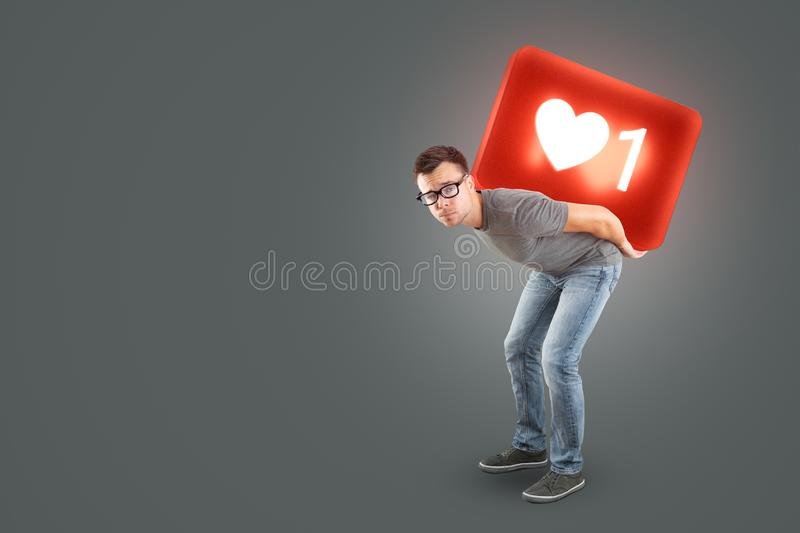 Man carrying a large social media Like Symbol on his back. A man in jeans and t-shirt is carrying a 3d rendered social media like symbol on his back. Cut out on stock photos