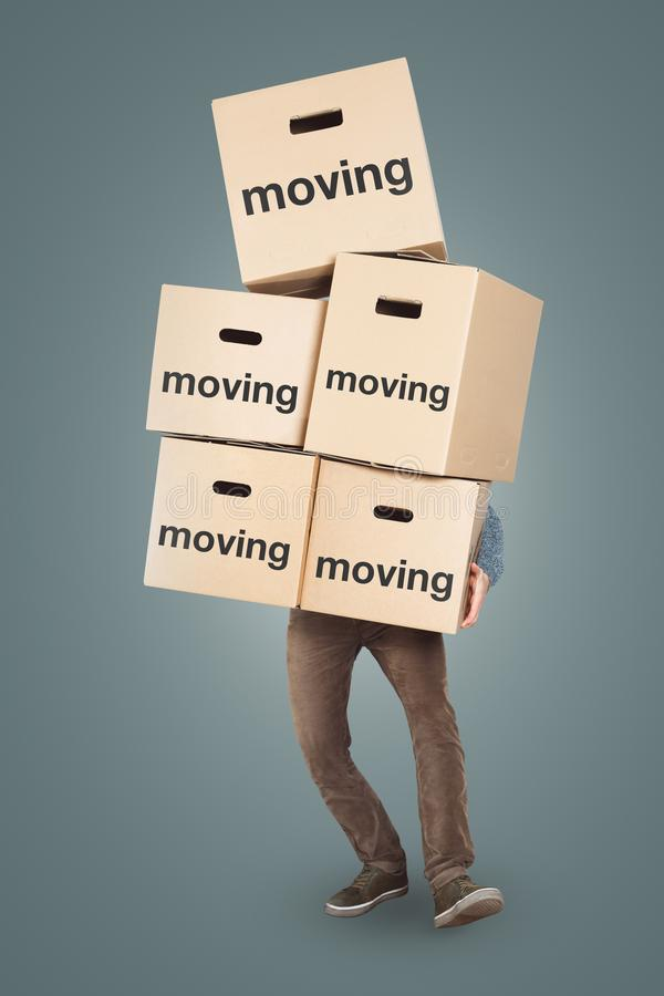 A man is carrying many moving boxes - isolated on a neutral background royalty free stock photography