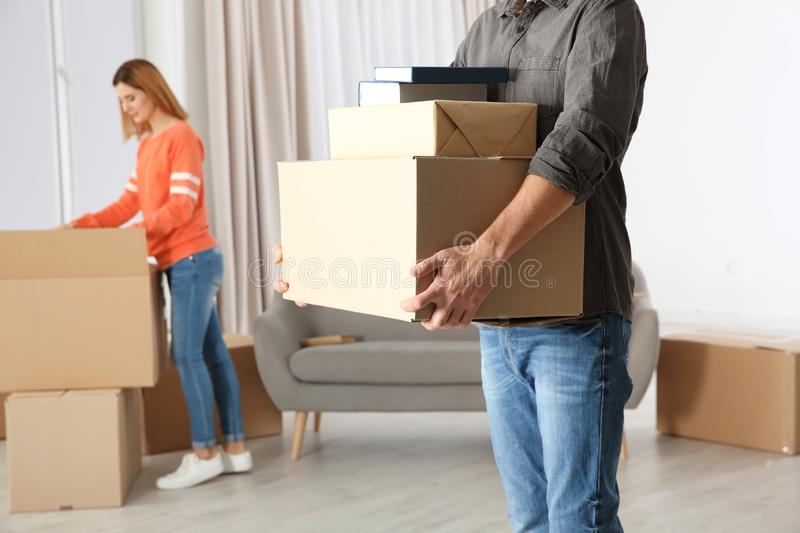 Man carrying moving boxes while woman unpacking other stock images