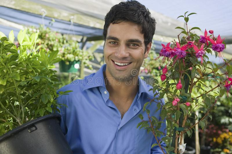Man Carrying Plants stock photography