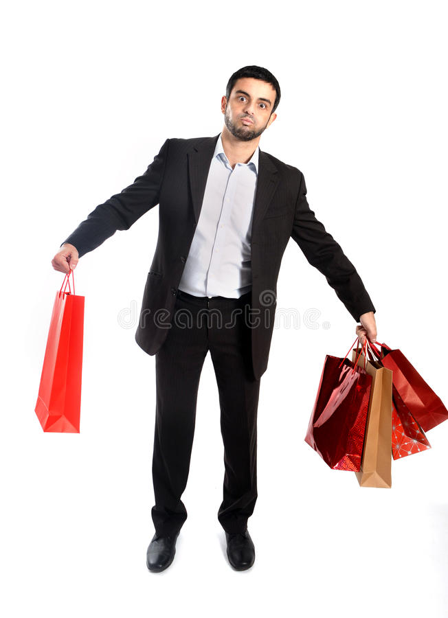 Man carrying sale shopping bags in stress. Attractive Man carrying lots of Shopping Bags in Stress royalty free stock photo