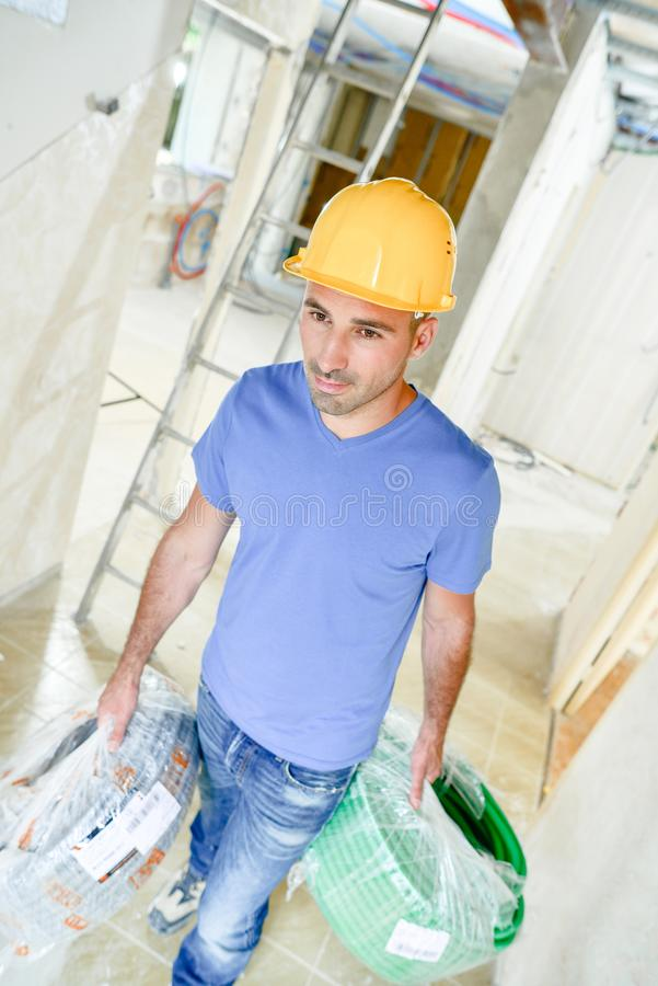 Man carrying spools electrical cable. Man carrying spools of electrical cable royalty free stock photo