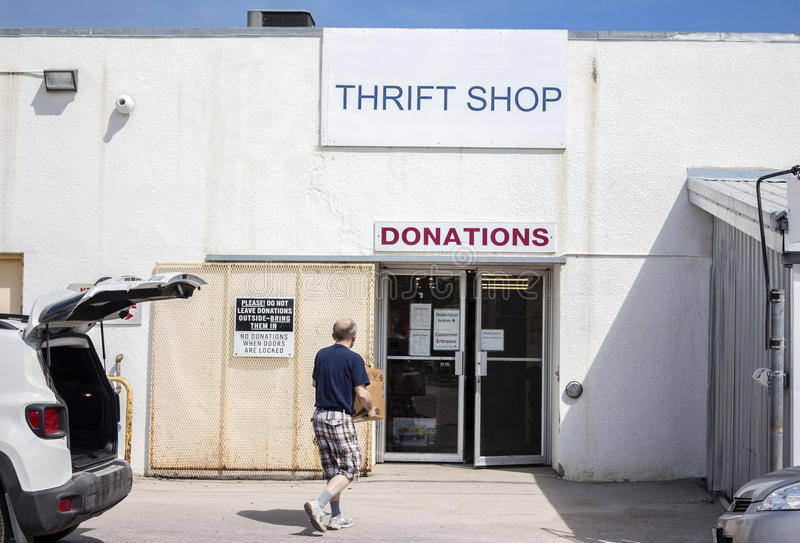 Man carrying vintage items into a thrift shop. Horizontal image of a man carrying donated items into a thrift store royalty free stock photo