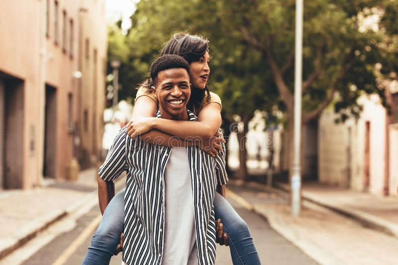 Couple enjoying themselves outdoors. Man carrying a women on his back. Couple piggybacking outdoors on city street royalty free stock images