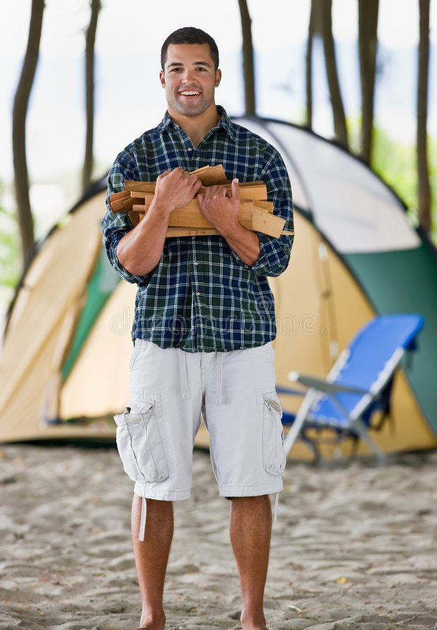 Man carrying wood at campsite. Man carrying wood to his campsite royalty free stock images