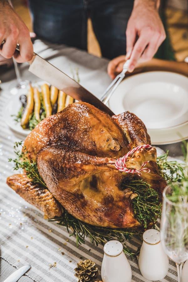 Man carving roasted turkey stock image