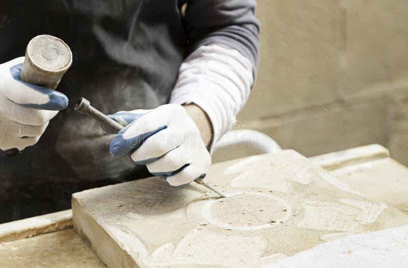 Man carving stone stock photo