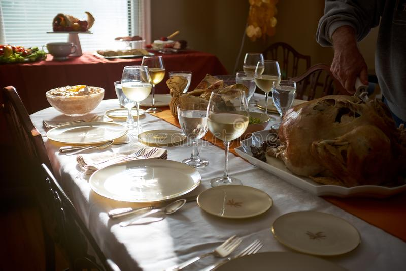 Man carving a turkey at a Thanksgiving table royalty free stock photo
