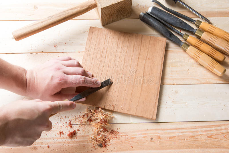 Man carving wood with handtools. Man carving wood with many handtools on the bench stock images