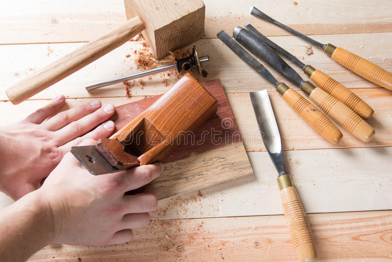 Man carving wood with handtools. Man carving wood with many handtools on the bench stock photo