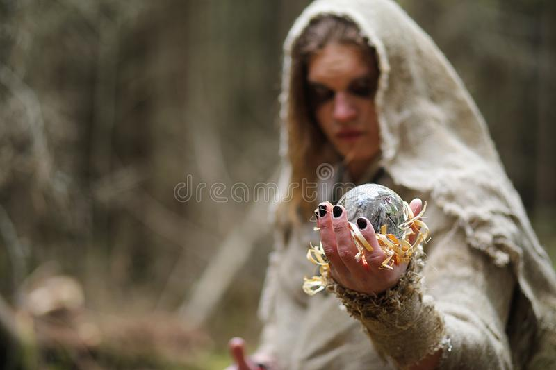 A man in a cassock spends a ritual in a dark forest. With a crystal ball and bookrr stock image