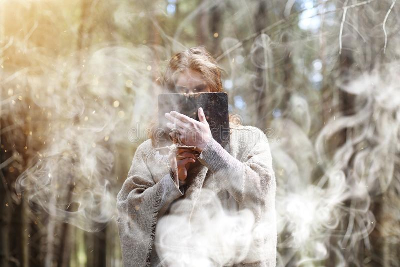 A man in a cassock spends a ritual in a dark forest. With a crystal ball and bookrr royalty free stock photo