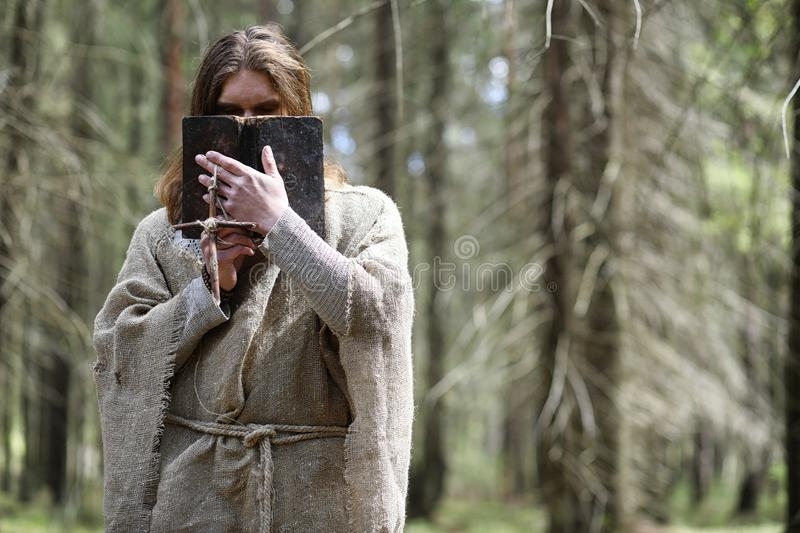 A man in a cassock spends a ritual in a dark forest. With a crystal ball and bookrr stock photos