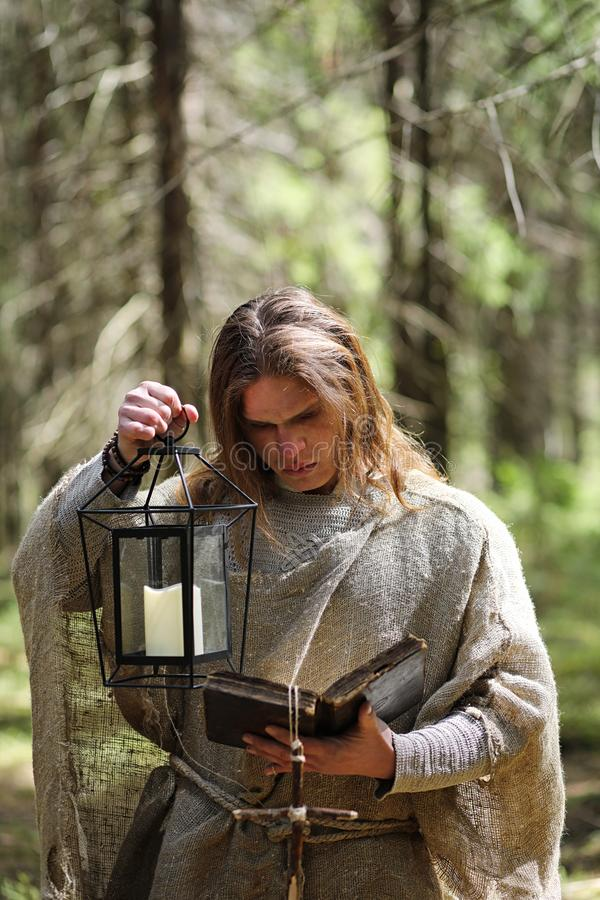 A man in a cassock spends a ritual in a dark forest. With a crystal ball and bookrr stock photography