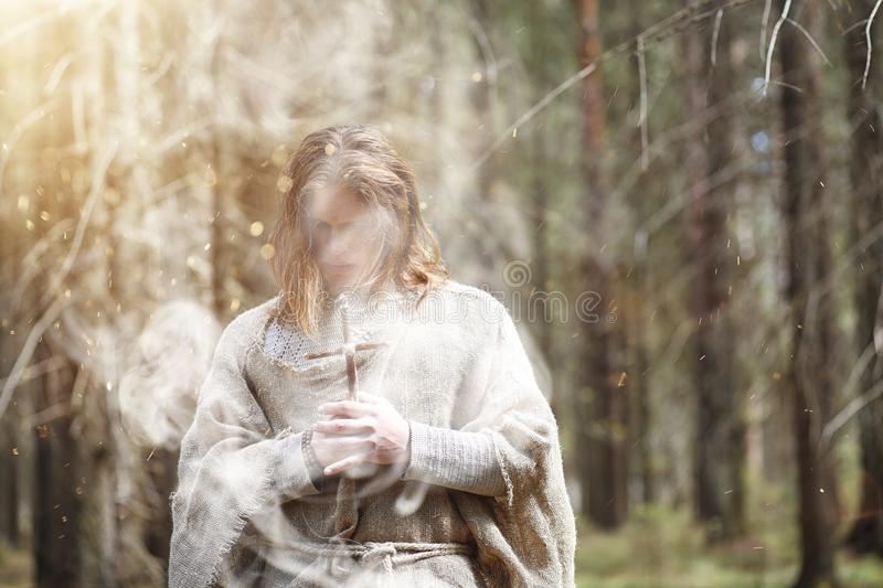 A man in a cassock spends a ritual in a dark forest. With a crystal ball and bookrr royalty free stock photography