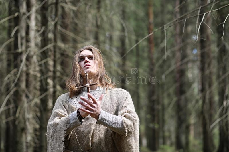 A man in a cassock spends a ritual in a dark forest. With a crystal ball and book stock photography