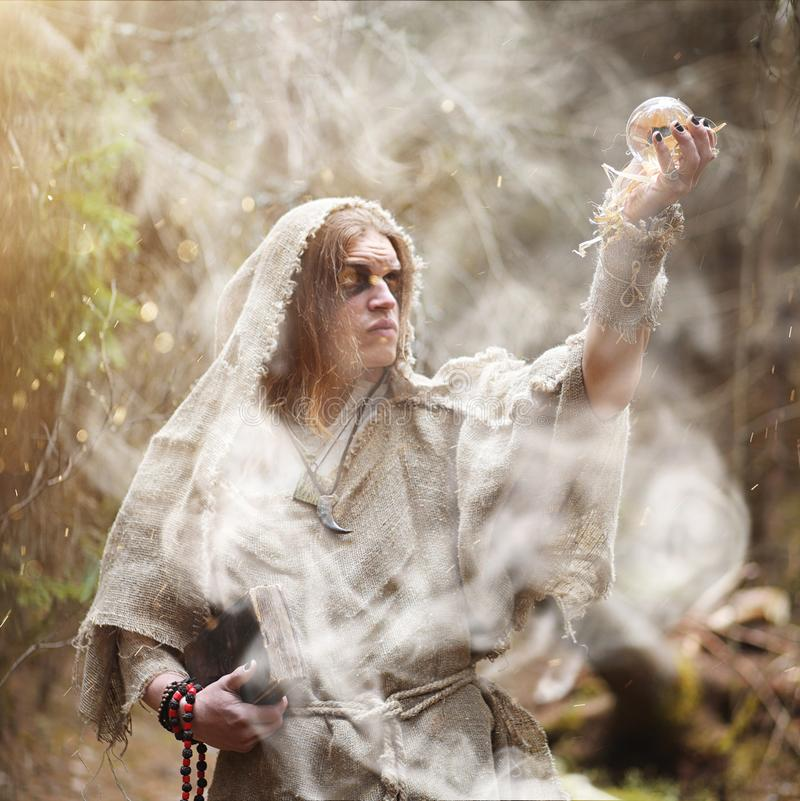 A man in a cassock spends a ritual in a dark forest. With a crystal ball and bookrr royalty free stock images