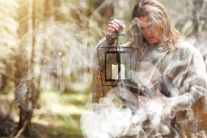 A man in a cassock spends a ritual in a dark forest. With a crystal ball and bookrr stock images