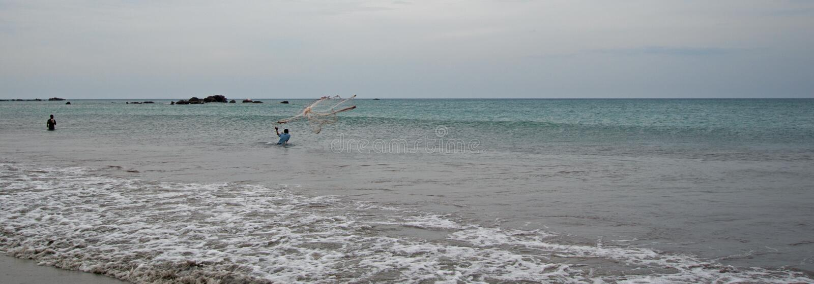 Man casting fishing net on Nilaveli beach in Trincomalee Sri Lanka. Asia stock photos
