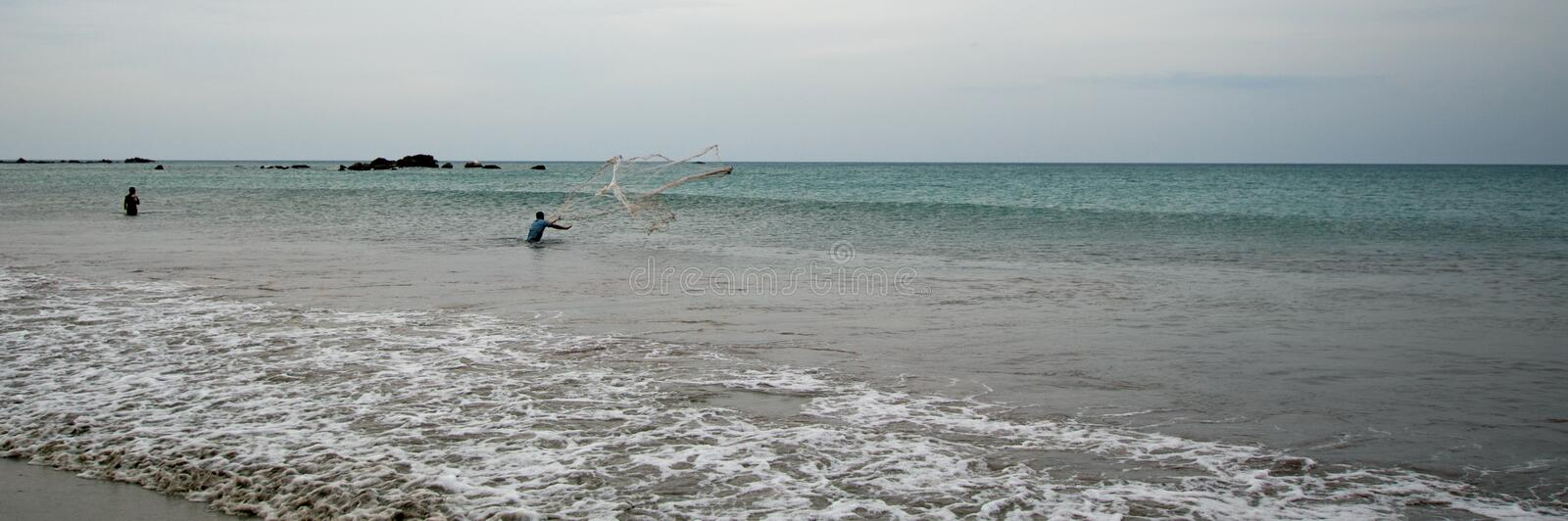 Man casting fishing net on Nilaveli beach in Trincomalee Sri Lanka. Asia royalty free stock photos