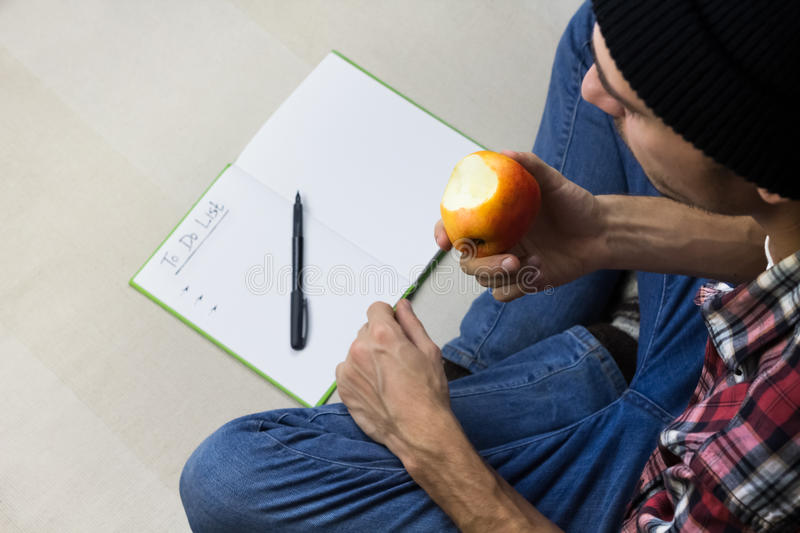 Man in casual clothes eats apple royalty free stock photos