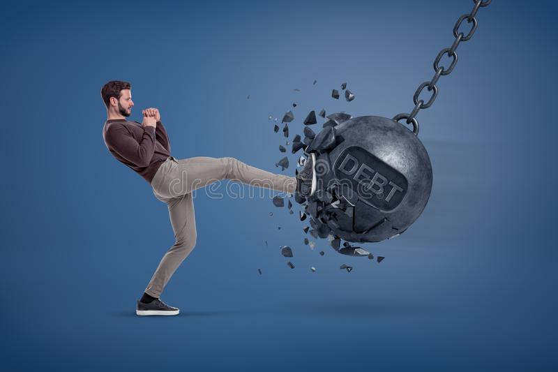 A man in casual clothes kicks a giant wrecking ball with a word DEBT written on it. stock photography