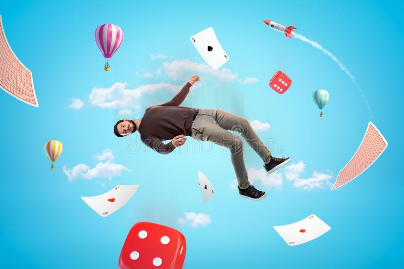 Man in casual clothes with red casino dice, playing cards, hot air balloons and silver red space rocket in the air on royalty free stock photography